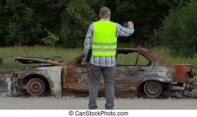 Inspector take pictures of burned down car wreck on the side...
