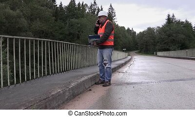 Worker talking on cell phone on bridge