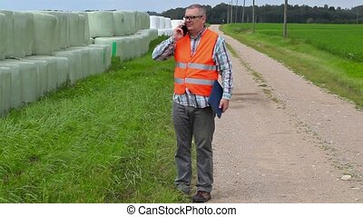 Farmer talking on smart phone and walking near hay bales