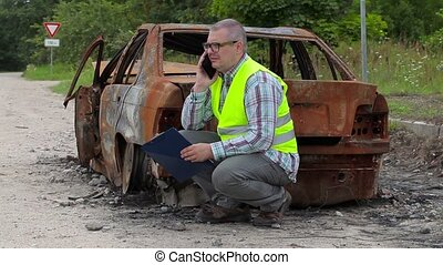Inspector talking on smart phone near burned down car wreck...