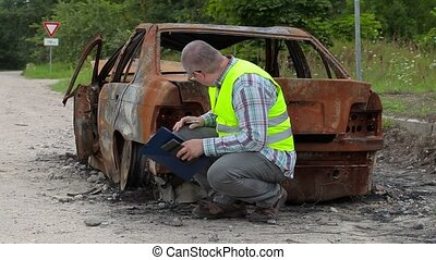 Inspector checking and writing near burned down car wreck on...