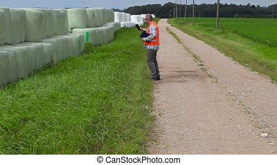 Farmer using tablet PC and walking near hay bales