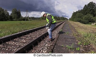 Railroad worker using tablet PC and walking near railway