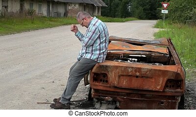 Stressful man on burned down car wreck on the side of the...