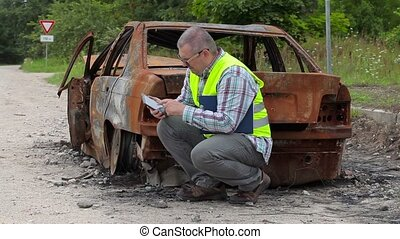 Inspector using tablet PC near burned down car wreck on the...