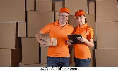 Couriers in orange uniform standing against brown carton stacks backround. Delivery company staff