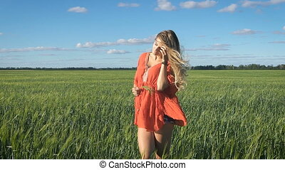 Beautiful young blond woman with the sexy look standing and enjoying herself at a green field