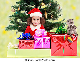Little girl near the Christmas tree surrounded by gifts -...