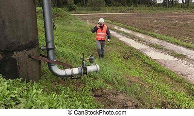 Engineer talking on phone and walking near the pipe