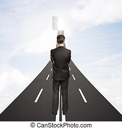 Success concept - Young businessman standing on road leading...