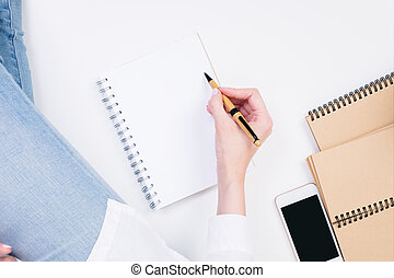 Woman writing in notepad closeup - Top view of woman's hand...