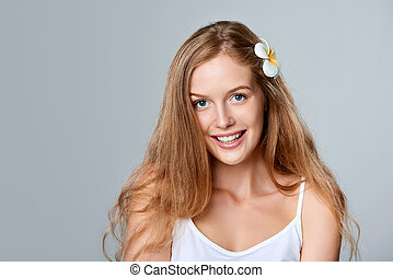 Beautiful young woman with flower in hair - Beauty portrait...