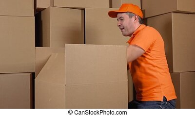 Warehouse worker in orange uniform packaging big carton with duct tape gun. Multiple boxes background. 4K video