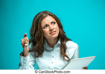 The displeased young business woman with pen and tablet for notes on blue background