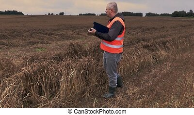 Farmer checking destroyed and wet cereal field