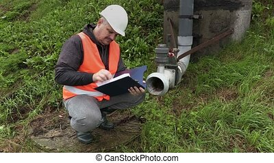 Engineer with documentation near the dirty pipe