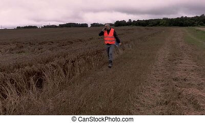 Farmer talking on phone and walking on destroyed and wet...