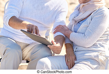 close up of senior couple with tablet pc on beach - family,...