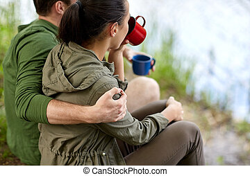 happy couple with cups drinking in nature - travel, tourism,...