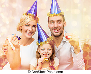 smiling family in blue hats blowing favor horns -...