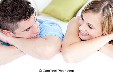 young couple looking at each other laying on the floor
