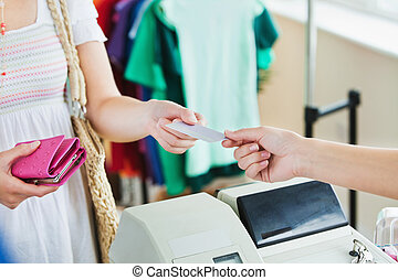 Close-up of a caucasian woman paying with her credit card in...