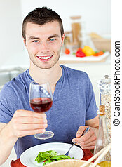 Cute man eating a healthy salad with some wine