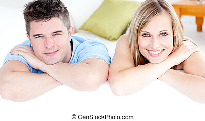 Affectionate couple ooking at the camera on a sofa