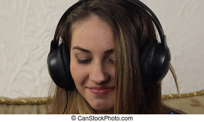 Attractive young woman listening music on smartphone sitting...