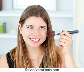 Portrait of a delighted woman using a powder brush in the...