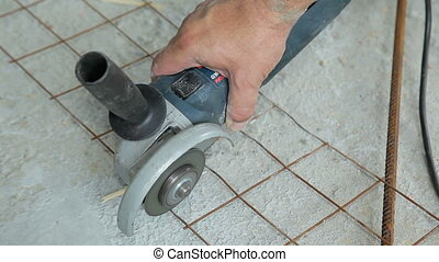 Worker cutting metal grid with angle grinder - Worker...