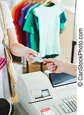Close-up of a cute woman paying with her credit card in a...
