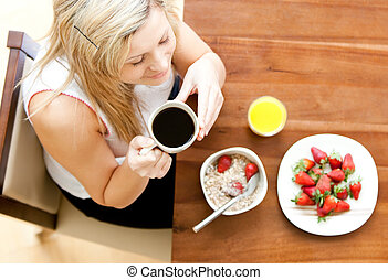 Cute young woman drinking coffee eating cereals and...