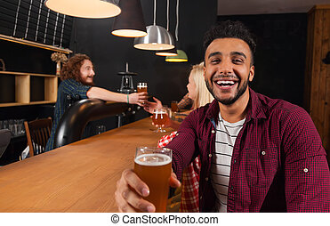 Young People Group In Bar, Hispanic Man Hold Glass Toasting...