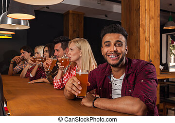 Young People Group In Bar, Drink Beer, Hispanic Man Hold...