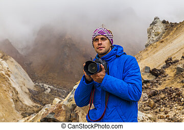 Young photographer on the background of volcanic rocks...