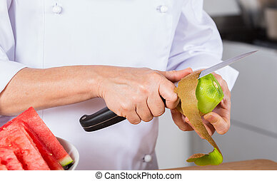 Chef with fruits - Chef cutting a delicious ripe kiwi