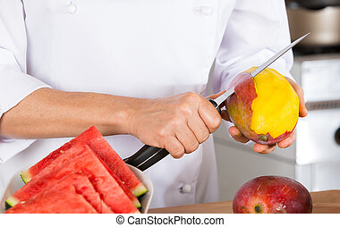 Chef with fruits - Chef cutting a delicious ripe mango