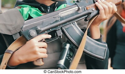 The Child in a Body Armor with a Machine Gun in his Hand