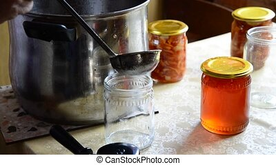 Housewife pours homemade jam in jar - Housewife pours...