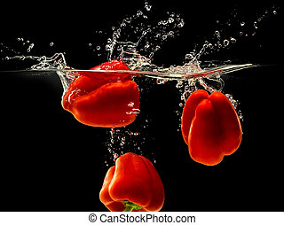Group of bell pepper falling in water on black - Group of...