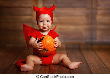funny baby in devil halloween costume with pumpkin on a dark...