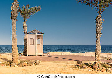 Palms and guard booth by the sea