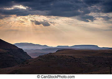 Dramatic sky, storm clouds and sun rays glowing over valleys, canyons and table mountains of the majestic Golden Gate Highlands National Park, major travel destination and tourist attraction in South Africa.