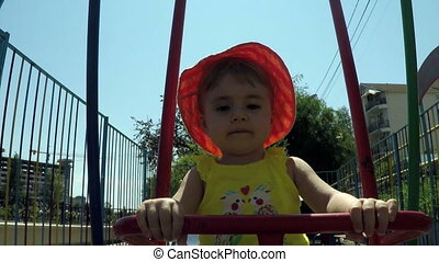 clouse-up portrait small child on a swing on a background of the sun on a blue sky