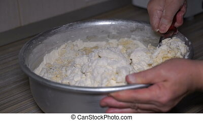 Footage woman kneads dough in a dish.