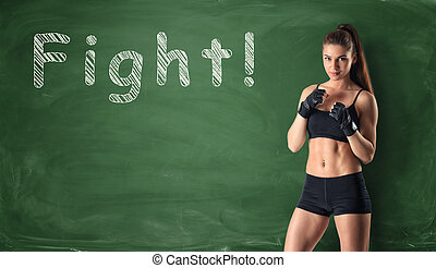 Fitness girl clenching her fists ready to fight on the...