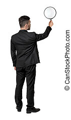 Back view of a businessman holding big magnifying glass in...
