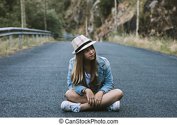 girl sitting on the road with hat