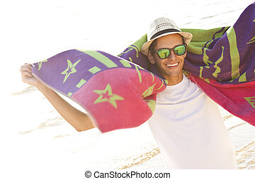 young man with the towel on the beach smiling